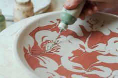 Debbie Wald surface decoration technique.  It appears to be stencils onto greenware, bisqued, then slip trailed and re-fired