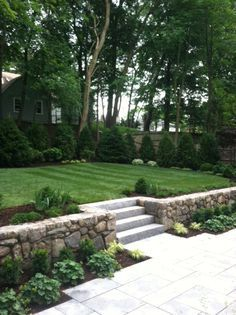 Cobblestone retaining wall with tiled patio and steps, and planted beds