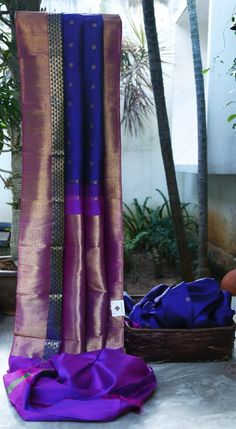 CLASSY NAVY BLUE KANCHIVARAM SILK HAS GOLD ZARI BUTTAS ALL OVER. THE NAVY BLUE, VIOLET WITH GOLD ZARI BORDER AND THE INTRICATE VIOLET PALLU GIVES THE SAREE MAGNIFICENT LOOK.