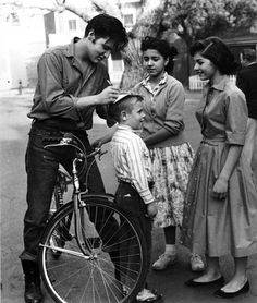 Elvis Presley riding a bike, stops to sign autographs for fans in Germany in 1959.    Library of Congress
