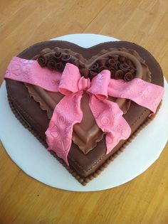 "Heart shaped cake made from 8"" square and 8"" round layers, covered in chocolate satin ice with ribbon roses and a pink fondant bow. Here's how I made it: http://www.youtube.com/playlist?list=PLt2Q49Q7hH9ohdWXKF6PRK1bMxjyyUl-R"