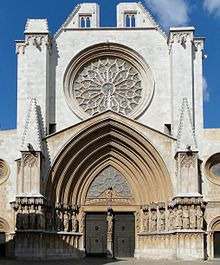 This is the Tarragona Cathedral which stands in Tarragona, Spain.  On either side of the Gothic pointed archway we can see the 12 apostles and Jesus in the middle.  These twelve apostles- except Judas are all saints in the Christian religion.  It is a holy reminder to those both passing by and entering the Cathedral.