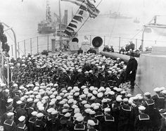 """President Theodore Roosevelt (standing on 12"""" gun turret at right). Addresses officers and crewmen on the after deck of USS Connecticut (Battleship # 18), in Hampton Roads, Virginia, upon her return from the Atlantic Fleet's cruise around the World, 22 February 1909."""