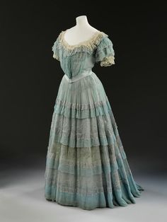 1905 Carresaute by Lucile, London. Two-piece evening dress, bodice and skirt, blue silk chiffon, lavishly trimmed with cream lace, pink silk ribbon rosebuds, metallic embroidery, and self-fabric ruffles and frills. Mounted on boned cream silk bodice lining and satin skirt lining. Via V.