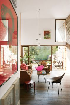 Pops of color can be found through this entire home which is located in Sydney, Australia. The base is neutral but color has been added by means of artwork, cushion, books and a bathroom wall painted in a yellow. The mural on the entry door (last image) is an homage to the Australian garage doors of the 50s and 60s. Found viaTHE STYLE FILES