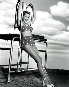 Virginia Mayo, classic pose and attire from the golden age of the #pinup.  Hard lighting common to the era with lovely matte work as the background cloudscape. #blackandwhite #hollywood #glamour