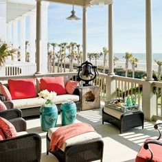 The porch with a ocean view  has synthetic wicker furniture, which is best for the coastal elements. Bright red pillows and turquoise tables add color to the space.