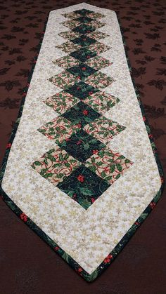 Get your home ready for the Holidays with this beautiful table runner. Red, green and gold, all the colors to reflect the Christmas spirit. The runner measure 60 long and 14 wide and would fit great on a dinning room table or a side board. 100% quality cotton. Perfect for your