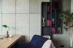 Detail pracovny: geometrické linie, beton a klasická lampa, vše dohromady funguje i díky umírněné barevnosti.