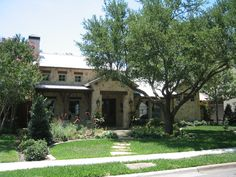 Modern Texas Ranch style: stone, wood, porches, deep overhangs, raised ridge metal roof