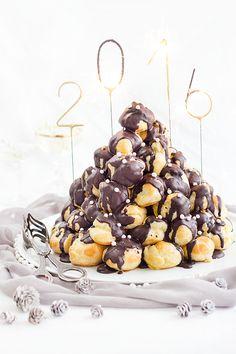 Ein französischer Klassiker: Croque en bouche. Ein Turm aus Profiteroles (Windbeuteln) mit Mandelkrokantfüllung. Traditionell mit Karamell zusammengehalten, bei mir mit Schokolade.
