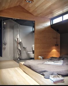 Modern Minimalist Bedroom Design Side By Side With Suite Bathroom And Separated With Glass Doors.