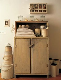 The off-centered wooden box on the wall balances nicely with the tall stack of textiles in the cabinet.