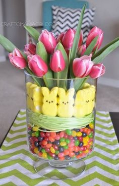 Cute Easter table centerpiece idea.  A large glass jar with tulips, marshmallow yellow bunnies and jelly beans.