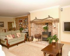 photo of beige white lounge with brick fireplace fireplace fireplace surround wood burner