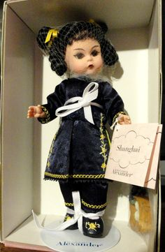 """View 1 of Madame Alexander's """"Shanghai Doll."""" She is so gorgeous with her embroidered Asian outfit and the shoes were also embroidered. She also comes with some Asian Chasu Bao food in a bamboo bowl...and what I believe a bracelet with adventurine semi precious stones...not so sure since I didn't open the plastic that it's in."""