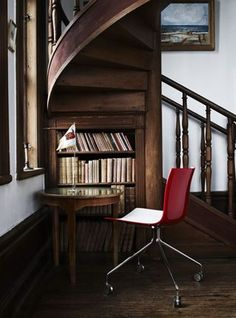 Bookcase and reading nook under a spiral staircase.   What a neat idea for conserving and enjoying a space.