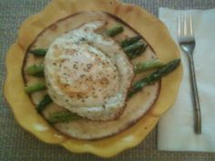 Tortilla with melted swiss cheese with pan-seared asparagus topped with a fried egg.