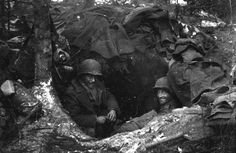 Two American soldiers in a foxhole during the Battle of the Bulge in Belgium, January 1945. By Tony Vaccaro. [1600x1044]