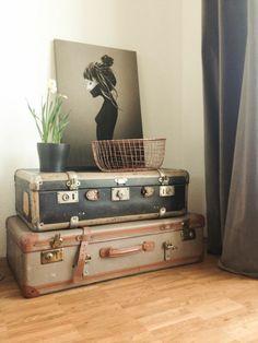 Juniqe Print fürs Wohnzimmer auf Vintage Koffern mit einer Kupferschale und Frühlingsblumen
