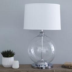 Sophisticated and elegant, this beautiful glass ball table lamp just oozes style. Substantial in size, it will make an impressive finishing touch to any room and bring a sleek contemporary look to your space. Made from glass with a gleaming chrome neck, base and inner column, it comes complete with a 17� crisp white linen shade. Perfect for a lounge or dining area placed on a console or sideboard. Please note that there may be tiny bubbles evident in the glass - these are not considered a…