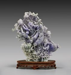 "Large and finely openwork carved, Chinese pale green and lavender jadeite group; depicting birds perched amid flowering vines of eggplants, above large chrysanthemums and rockery at the base; the jadeite of good purplish-lavender and pale green coloration; H: 13 1/2""; wood stand;"