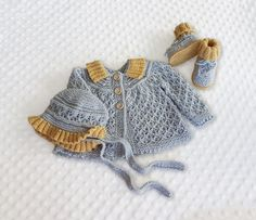 A lovely cardigan pattern with a matching hat and booties!