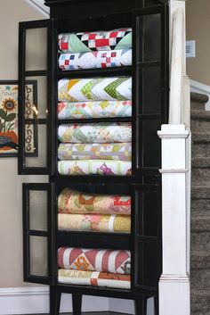 Repurpose a curio cabinet to house beautiful quilts that meet your personal style. These bright and bold patterened quilts are gorgeous. Plus its practical decor in case the electric goes out in the winter or you hear of a family in need. Colchas Quilting, Sew Kind Of Wonderful, Blanket Storage, Diy Quilt Storage, Storage For Blankets, Diy Storage, Storage Baskets, Towel Storage, Quilt Display
