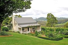 """""""Australian Country Estate,"""" this is the guesthouse on the grounds, its a 1 bedroom white cottage that was an original farm structure built in the early 20th century, the early 1900s with a classic metal/tin roof and picket fence style porch railings . surrounded by beautiful gardens and a citrus orchard $5,700,000"""