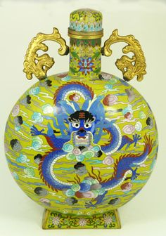 CHINESE QING CLOISONNE DRAGON MOON FLASK VASE  Antique Chinese Qing Dynasty cloisonne moon flask vase depicting blue dragon with wind and clouds over mustard yellow ground. Has figural dragon handles to shoulders.