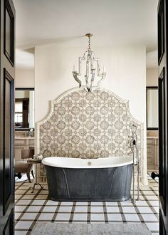 Large Bathroom with Dark Metal Tub containing: Curved Wall Tile with Vintage Chandelier also Tile Flooring plus Floor Mount Tub Faucet together with Dark Wooden Door