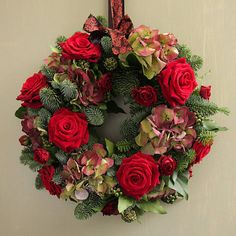 This festive wreath would be lovely for a Christmas wedding with a red theme - hydrangeas and roses with seasonal foliage.