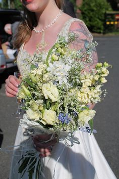 Bridal bouquet of delphiniums, hydrangeas, grape hyacinths, narcissus, dill, gypsophila, grasses, and roses.