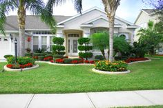 Cheap Landscaping Ideas For Front Yard Front yard landscape plans with red flowers and trees plus beautiful white house.Front yard landscape plans with red flowers and trees plus beautiful white house. Cheap Landscaping Ideas, Residential Landscaping, Florida Landscaping, Home Landscaping, Tropical Landscaping, Front Yard Landscaping, Landscaping With Palm Trees, Privacy Landscaping, Front Garden Landscape