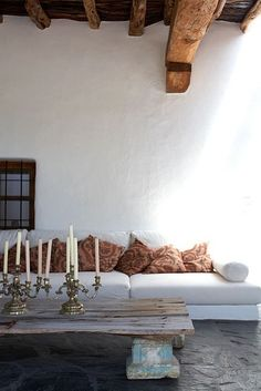 Love the old beams with the white walls and sofa with the rustic table and the candle sticks. Great combination.