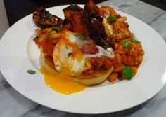 Frontier Beans with Poached Eggs - slow cooked homemade baked beans served with toasted bagels, poached eggs and crispy bacon.