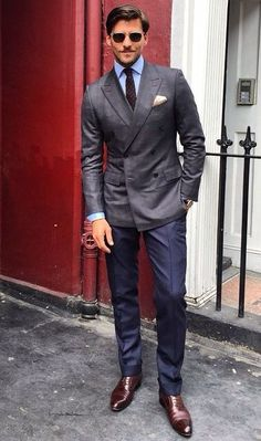 Shop this look on Lookastic:  https://lookastic.com/men/looks/double-breasted-blazer-dress-shirt-dress-pants-oxford-shoes-tie-pocket-square-sunglasses-watch/13328  — Dark Brown Sunglasses  — Dark Brown Polka Dot Tie  — Light Blue Dress Shirt  — Beige Pocket Square  — Charcoal Double Breasted Blazer  — Black Leather Watch  — Navy Dress Pants  — Dark Brown Leather Oxford Shoes