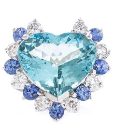 An 18 Karat White Gold, Aquamarine, Diamond and Sapphire Ring, containing one heart shape mixed cut aquamarine weighing approximately 8.25 carats, eight round brilliant cut diamonds weighing approximately 0.76 carat total and seven round mixed cut sapphires.
