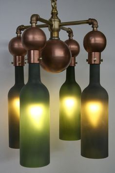 This chandelier is constructed of plumbing parts and four sandblasted wine bottles. The bulbs are energy efficient LED bulbs. To change the bulbs, I include with each purchase a recycled cardboard plastic wrap tube that is inserted around the bulb and turn.