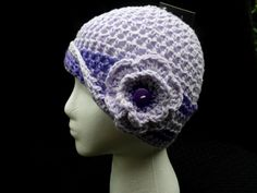 This crocheted cloche/beanie type hat is done in a lavender and purple yarn. It has a 3-dimentional matching flower with a button at the