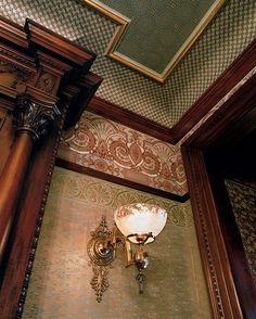 Photo shows the wonderful carved wood typical of Victorians and how high molded ceilings let you be creative with period wallpaper. Nice sconce, too.