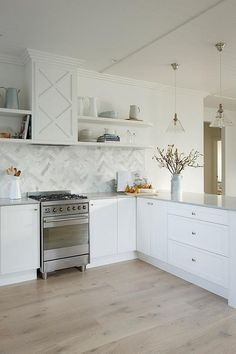 Chic kitchen features white shaker cabinets paired with light gray quartz countertops, Caesarstone Clamshell Quartz, and a marble herringbone backsplash. Outdoor Kitchen Countertops, Kitchen Tiles, New Kitchen, Kitchen Cabinets, Kitchen Modern, Kitchen Colors, Country Kitchen, Backsplash With Dark Cabinets, Backsplash Ideas