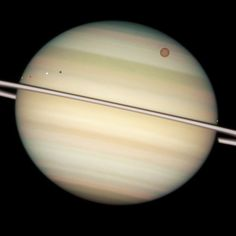 The giant orange moon Titan — larger than the planet Mercury — can be seen at upper right. The white icy moons that are much closer to Saturn, hence much closer to the ring plane in this view, are, from left to right: Enceladus, Dione, and Mimas. The dark band running across the face of the planet slightly above the rings is the shadow of the rings cast on the planet