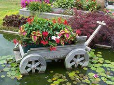 idées pour un jardin gai - chariot en bois massif avec plantes vertes dans le bassin aquatique