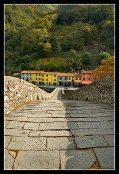 "This old medieval bridge is Ponte della Maddalena (Bridge of Mary Magdalene) also known as Ponte del Diavolo, the ""Bridge of the Devil"". The bridge crosses the Serchio river near the town of Borgo a Mozzano, Tuscany, Italy."