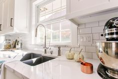 Timeless white modern kitchen remodel featuring Elkay's quartz charcoal sink, Avado faucet, Brittanicca Cambria Quartz countertops, white subway tile | construction2style