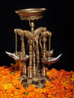 Standing 4-Parrots Holding Brass Lamp   This beautiful brass lamp will transport you to a traditional courtyard in South India even as it brightens up your home, especially now, when the 'festival of lights' is around the corner.