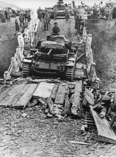 German medium tank Pz.Kpfw.III Ausf. F overcomes heavily damaged bridge. On the bridge, to facilitate the passage of troops, laid wooden beams and boards. In the background there is a tank column waiting for the march. Tank column of the 2 nd Panzer Division. The tank is rearmed with a 50-mm gun KwK 38 instead of a regular 37-mm cannon.