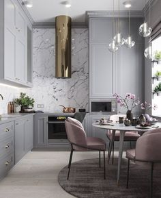 Modern grey kitchen with marble back splash and round kitchen table