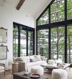 Living room design: white shiplap, black windows, aged wooden ceiling beams, transitional and fresh decor